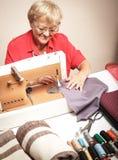 Starsza kobieta szy na szwalnej maszynie obraz stock
