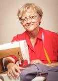 Starsza kobieta szy na szwalnej maszynie obrazy stock