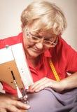 Starsza kobieta szy na szwalnej maszynie zdjęcie stock
