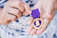 Starsza kobieta Trzyma Militarnego Purple Heart medal W Jej ręce zdjęcia royalty free