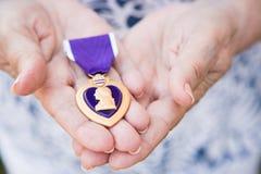 Starsza kobieta Trzyma Militarnego Purple Heart medal W Jej ręce obraz stock