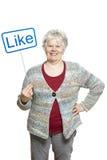 Starsza kobieta trzyma ogólnospołeczni środki podpisuje uśmiecha się Zdjęcia Stock