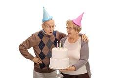 Starsza kobieta trzyma urodzinowego tort i starszego mężczyzna dmuchanie Obrazy Stock