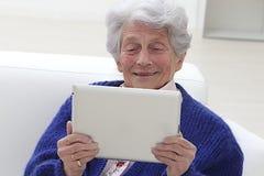 Starsza kobieta uśmiechnięta i patrzeje jej laptop Zdjęcia Stock