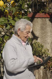 Starsza kobieta używa cyfrowego podołek obraz royalty free