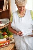 Starsza kobieta używa pastylkę w jej kuchni Zdjęcie Stock