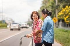 Starsza kobieta używa piechura krzyża ulicę Zdjęcia Royalty Free