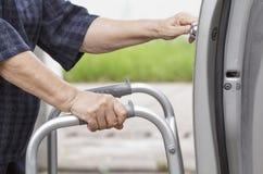 Starsza kobieta używa piechura przy parking samochodowym Zdjęcia Royalty Free