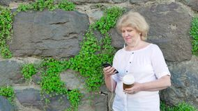 Starsza kobieta używa smartphone i pijący kawę Rocznik ściana dziki kamień w tle zbiory wideo