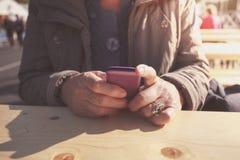 Starsza kobieta używa smartphone outdoors Obraz Royalty Free