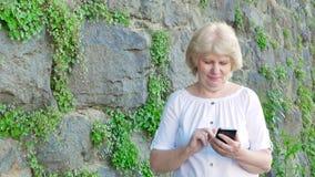 Starsza kobieta używa smartphone Rocznik ściana dziki kamień w tle zbiory wideo