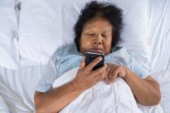 Starsza kobieta używa telefon komórkowego na łóżku Fotografia Royalty Free