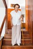 Starsza kobieta używa trzciny dostawać puszkowi schodki w domu zdjęcia royalty free