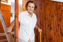 Starsza kobieta używa trzciny dostawać puszkowi schodki w domu obraz royalty free