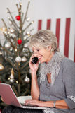 Starsza kobieta używa telefon na wigilii Fotografia Stock