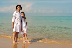 Starsza kobieta w białej sukni z piękną dziewczyną w białej sukni na morzu Poj?cie pogodny i szcz??liwy lato obrazy stock