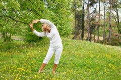 Starsza kobieta w białych rozciąganie rękach zdjęcie royalty free