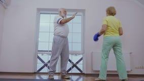 Starsza kobieta w bokserskich rękawiczkach trenuje z jej mężem zbiory wideo