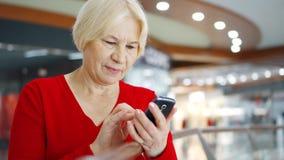 Starsza kobieta w centrum handlowego use telefonie komórkowym Żeński kupujący wyszukuje na telefonie komórkowym w centrum handlow zbiory