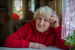 Starsza kobieta w czerwonym kurtki obsiadaniu przy stołem Obraz Royalty Free
