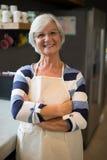 Starsza kobieta w fartuch pozyci w kuchni obraz stock