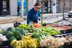 Starsza kobieta w kapeluszu sprzedawania owoc i warzywo przy miejscowego rynkiem w Esporles, Mallorca, Hiszpania obrazy stock