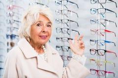 Starsza kobieta w okulisty sklepie obrazy royalty free