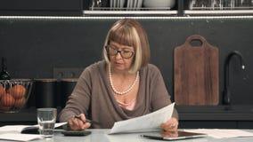 Starsza kobieta w szkłach rozważa koszty zbiory wideo