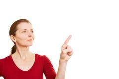 Starsza kobieta wskazuje z wskaźnikiem Obrazy Royalty Free