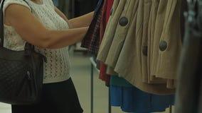 Starsza kobieta wybiera ona odzieżowa w supermarkecie zbiory wideo