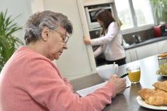 Starsza kobieta wydaje czas robi crosswords z domowym pomagierem w tle Zdjęcia Royalty Free