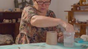 Starsza kobieta wyrównuje krawędź gliniany kubek zbiory