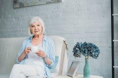 starsza kobieta z filiżanką aromatyczny kawowy odpoczywać na kanapie fotografia stock