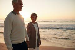 Starsza kobieta z jej mężem spaceruje na plaży zdjęcia royalty free