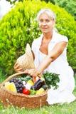 Starsza kobieta z koszem pełno zbierający owoc i warzywo fotografia royalty free