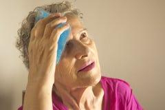 Starsza kobieta z lodem na głowie dla migreny fotografia royalty free