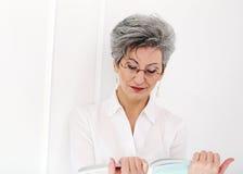 Starsza kobieta z magazynem Obraz Stock