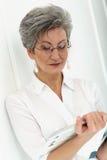 Starsza kobieta z magazynem Fotografia Royalty Free