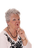 Starsza kobieta z palcem nad usta Obrazy Royalty Free