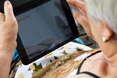 Starsza kobieta z pastylką Obraz Royalty Free
