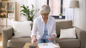 Starsza kobieta z pieniądze i rachunkami w domu zbiory