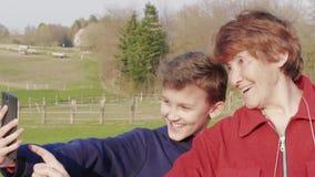 Starsza kobiety i nastolatka chłopiec bierze selfie wiszącą ozdobą, uśmiech zbiory wideo