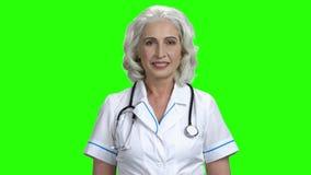 Starsza kobiety lekarka na zielonym parawanowym tle zdjęcie wideo
