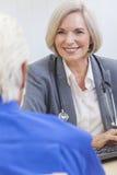 Starsza kobiety lekarka Z Męskim pacjentem Zdjęcia Stock