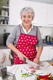Starsza lub stara kobieta z popielatym włosianym kucharstwem w kuchni Obrazy Royalty Free
