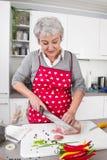 Starsza lub stara kobieta z popielatym włosianym kucharstwem w kuchni. Obraz Royalty Free