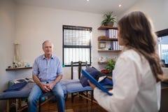 Starsza męska cierpliwa patrzeje kobiety lekarka z kartoteką Fotografia Royalty Free