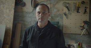 Starsza męska fachowa ciesielka mistrza pozycja przy drewnianymi manufaktura zwrotami kamera jest spokojny zbiory wideo