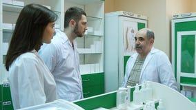 Starsza męska farmaceuta pomaga jego młodych kolegów przy apteką Zdjęcie Stock
