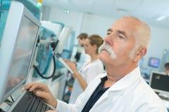 Starsza męska farmaceuta sprawdza rezultaty w białym lab Obraz Stock
